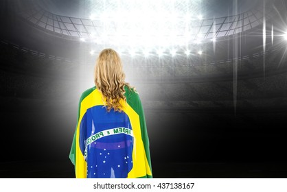 Athlete with brazilian flag wrapped around his body against american football arena