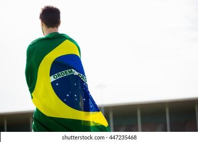 Athlete with brazilian flag wrapped around his body in stadium