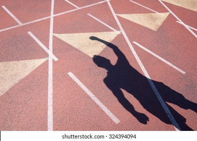 Athlete celebrating with a fist pump casts a shadow on a weathered red running track