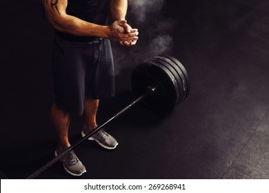 Athlete clapping hands with talc before deadlift barbells workout