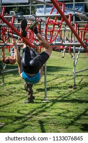 Athlete climbing along a low hanging rig obstacle at an obstacle course race