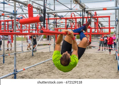 Athlete climbing along a pole at an obstacle course race