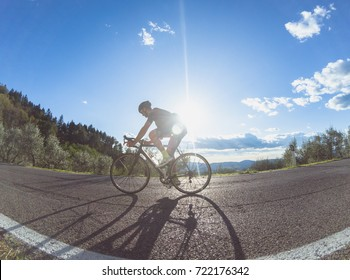 Athlete climbing a mountain road on a summer afternoon with a racing bicycle. Backlight shot with sun flare enhanced.