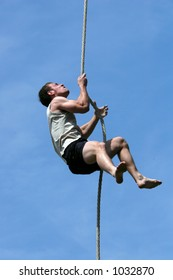 Athlete climbing up the rope.