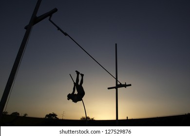Athlete compete in pole vault during sunset