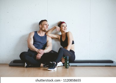 Athlete Pärchen lächeln nach gutem Training im Fitnessraum. Sportym-Konzept