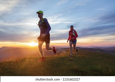 Athlete couple trail running in the hills during sunset. Shallow D.O.F. and with motion blur.