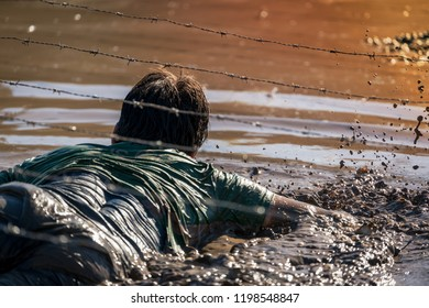 Athlete crawling in mud under barbed wire, obstacle course race