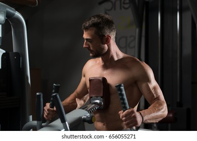 Athlete Doing Heavy Weight Exercise For Back On Machine