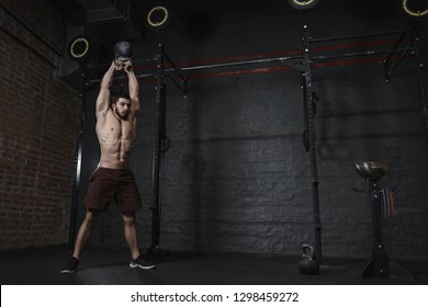 Athlete doing kettlebells swing exercise at cross fit gym. Handsome man doing functional training practicing workout. Copy space.