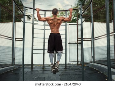 athlete doing pull-up on horizontal bar.Mans fitness at the stadium