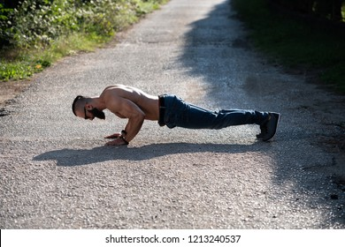 Athlete Doing Pushups Outdoors in Nature As Part Of Bodybuilding Training