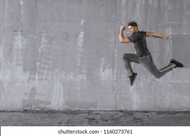 Athlete doing sprint hiit high intensity interval training. Male fitness model in fashion sportswear in city. Runner sprinting on urban gray background. Sport, workout, healthy lifestyle concept.
