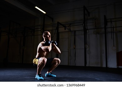 Athlete doing squat with kettlebells