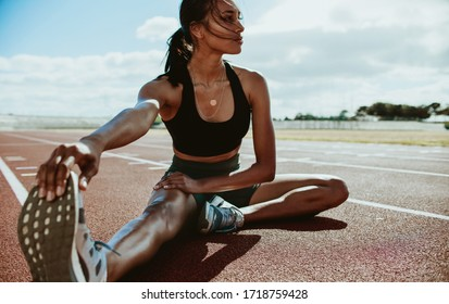 Athlete doing stretching exercises on running track. Woman runner stretching leg muscles by touching his shoes and looking away.