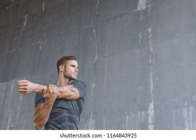 Athlete doing stretching warmup exercise. Male fitness model in fashion sportswear in city. Runner sprinting on urban gray background. Sport, workout, healthy lifestyle concept.