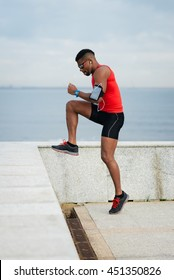 Athlete doing toe taps hiit exercise for warming up before running. Black young runner training towards the sea.