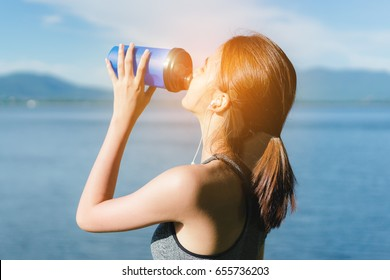 Athlete drinking protein shake nutrition,young girl asian and listen music after exercise running workout outdoor at beach seaside in summer for muscle building and slim fit body nice strong perfect.