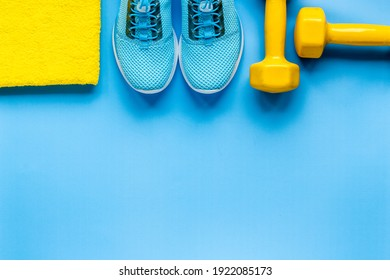 Athlete equipment with dumbbells and sneakers. Overhead view