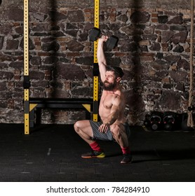 Athlete executing dumbbell snatch