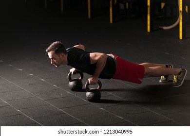 Athlete exercising push ups on kettlebells at the gym. Dark photography concept with copy space.