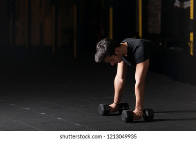 Athlete exercising push ups on dumbbells at the gym. Dark photography concept with copy space.