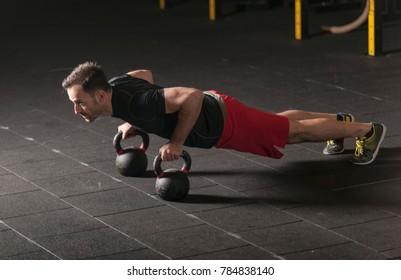 Athlete exercising push ups on kettlebells