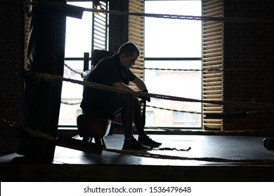 Athlete fighter boxer sits alone in a boxing ring