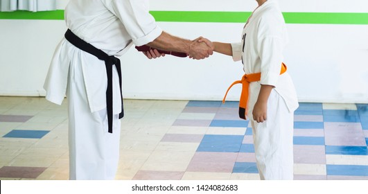 Athlete firmly shakes the Sensei's hand after receiving red Karate belt.