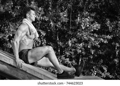 Athlete with fit body and towel on neck sitting on concrete surface on natural background. Fitness and sport. Hygiene and health concept, black and white