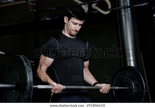 Athlete Fitness trainer working out / weight lifting in a gym