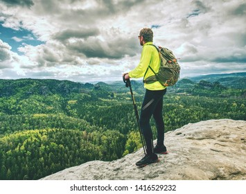 Athlete ginger hair man tourist hiking mountain trail, walking on sandstone rocky hill, wearing backpack and sunglasses, using trekking sticks. Tourism concept