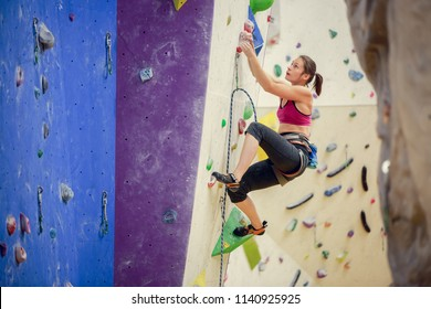 athlete girl climbing up purple wall for rock climbing