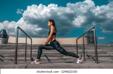 Athlete girl doing stretching before jogging in the morning in the city. Against the background of concrete stairs and clouds. The concept of a healthy lifestyle. In sportswear and sneakers.