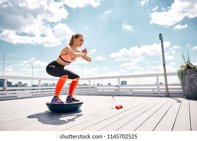 Athlete girl is enjoying work out with outfit on high balcony. She is doing squats on bosu platform while stretching resistance band under knees. Copy space in right side