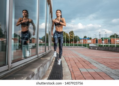 Athlete girl runs jump sports jogging training summer city. Headphones telephone. Concept fitness fresh air, active lifestyle workout. Free space. Morning evening motivation power spirit.