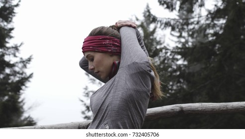 Athlete girl stretching warm up or cool down for running..Real people woman runner sport training in autumn or winter in wild mountain outdoors nature, bad foggy weather.