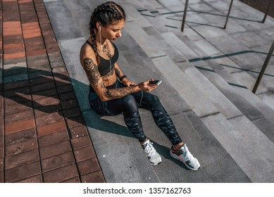 Athlete girl tattoos, sitting on steps summer city, hand smartphone, listening music with headphones. Resting after jogging workout. Concept of motivation, active life position healthy lifestyle.