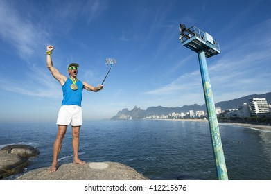 Athlete with gold medal posing for a celebratory selfie on a rock in Arpoador, in front of Ipanema Beach, Rio de Janeiro, Brazil