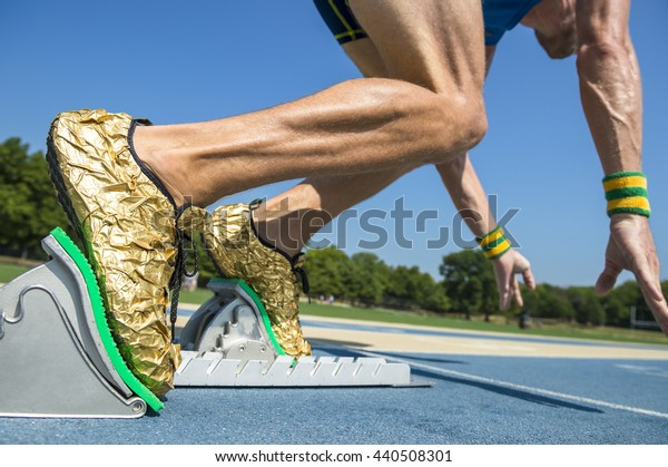 Athlete in gold shoes starting a race from the starting blocks on a blue running track
