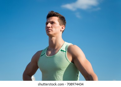 Athlete in green tshirt on sunny day. Sport and healthy lifestyle concept. Fitness model with muscular hands, biceps, triceps, strong muscles. Workout and training. Man bodybuilder posing on blue sky.