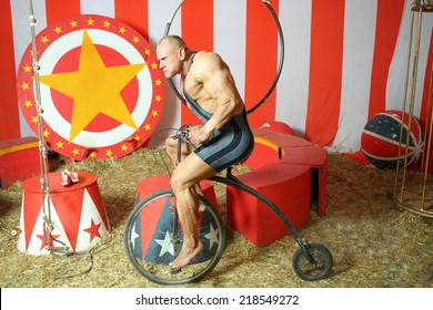 Athlete with grimace riding circus retro bike