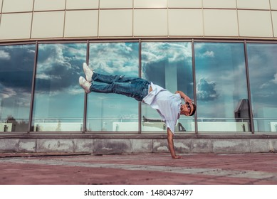 athlete guy dancer in white T-shirt, jeans, jump his arm, summer city, sunglasses, background glass windows, active hip hop youth lifestyle acrobatic stunt break dance, street and fashionable artist