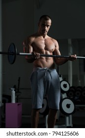 Athlete In The Gym Performing Biceps Curls With A Barbell