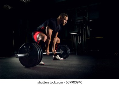 Athlete in the gym is prepared to perform an exercise called deadlift