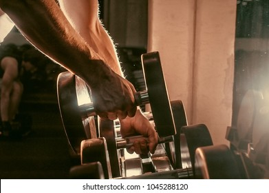 Athlete in the gym training with dumbbells. Toned image. Man is engaged with dumbbells on the bench. Hands with dumbbells. another view close