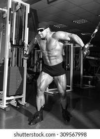 Athlete handsome bodybuilder training on simulator in the gym