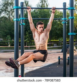 Athlete hanging on fitness station performing legs raises. Core cross training working out abs muscles