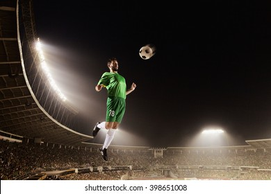 Athlete heading soccer ball in stadium
