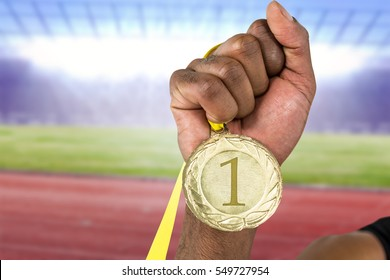 Athlete holding gold medal after victory against race track